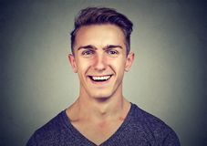 Happy young man laughing isolated on gray background royalty free stock photos