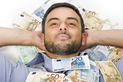 Happy Young Man laying on Banknotes Royalty Free Stock Images