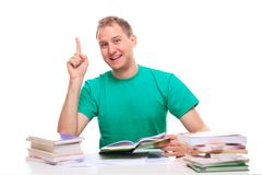 Happy young man learns at his desk Stock Photos