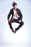 Happy young man in leather jacket jumps Royalty Free Stock Image