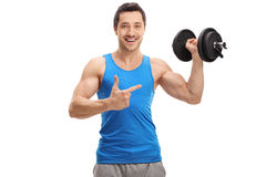 Happy young man lifting a dumbbell and pointing Stock Photos