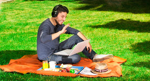 Happy young man listening music and wearing headphones with a picnic near of him in a park Royalty Free Stock Image