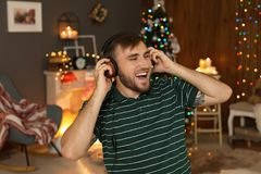 Happy young man listening to Christmas music. At home royalty free stock photo