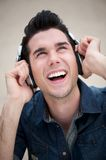 Happy young man listening to music on earphones outdoors Stock Photos
