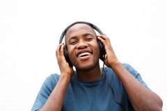 Happy young man listening to music on headphones Royalty Free Stock Photography