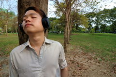Happy young man listening to music with headphones and leaning a tree in the public outdoor park. Stock Images