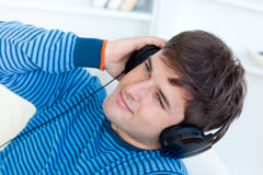 Happy young man listening to music on the sofa Royalty Free Stock Images