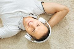 Happy young man listening to a nice song and smiling cheerfully. Amazing music. Positive young emotional man smiling cheerfully and feeling happy while relaxing Royalty Free Stock Images
