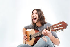 Happy young man with long hair playing guitar and singing Royalty Free Stock Photography