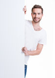 Happy young man look out from blank banner. Royalty Free Stock Photos