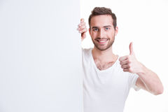 Happy young man look out from blank banner. Stock Photos