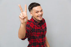 Free Happy Young Man Looking At Camera Showing Peace Gesture. Stock Photo - 96031070