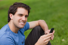 Happy young man looking at the camera while sending a text Royalty Free Stock Photography