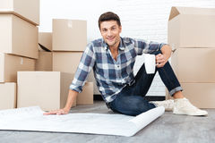 Happy young man looking at house blueprints Royalty Free Stock Photography