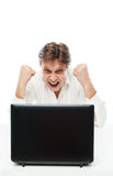 Happy young man looking at laptop and gesturing Royalty Free Stock Images