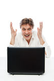 Happy young man looking at laptop and gesturing Stock Image