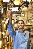 Happy young man looking at price tag of chandelier in lights store Royalty Free Stock Photography