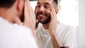Happy young man looking to mirror at home bathroom stock footage