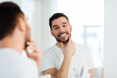 Happy young man looking to mirror at home bathroom Royalty Free Stock Photography