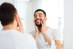 Happy young man looking to mirror at home bathroom Stock Images