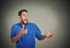 Happy young man looking to side while pointing at you, surprised by something Stock Images