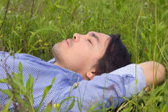 Young man lying on green grass. Happy young man lying on grass at sunny day Stock Images
