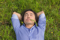 Young man lying on green grass Royalty Free Stock Images