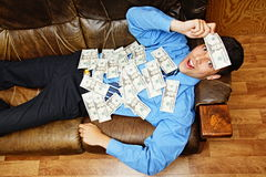 Happy young man lying with money Stock Photos