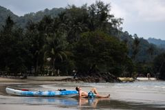 Happy young man lying near a kayak boat on Ko Chang, Thailand in April, 2018 - Best travel destination for happiness royalty free stock image
