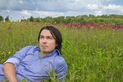Young man lying on a spring meadow Royalty Free Stock Photos