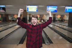 Happy young man made a bowling strike. The student raised his hands from joy while playing bowling. Bowling victory. Stock Images