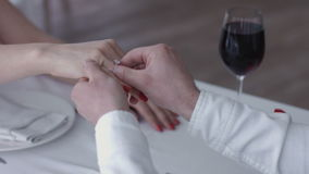 Happy young man making a proposal giving engagement ring to his fiancee in a restaurant ,close up hands stock video footage
