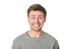 Happy young man with manic expression, on gray background Stock Photo