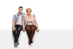 Happy young man and a mature woman sitting together on a panel. Happy young men and a mature women sitting together on a panel isolated on white background Royalty Free Stock Image