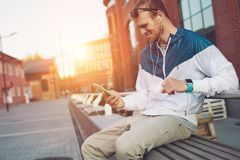 Happy young man with mobile phone and headset sitting on the bench. Outdoors Royalty Free Stock Image