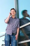 Happy young man on mobile phone outdoors Stock Photos