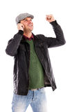 Happy young man with mobile phone receiving some great news. Over white background royalty free stock images