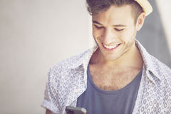 Happy young man with mobile phone Stock Image