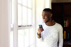 Happy young man with a mobile phone standing by a window Royalty Free Stock Photography