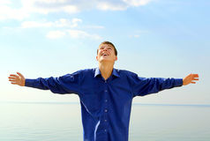 Happy Young Man outdoor. Happy Teenager with Hands Up on the Seaside Background Royalty Free Stock Photo