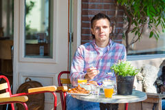 Happy young man in outdoors cafe at european city Stock Photos