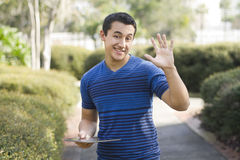 Happy young man outdoors. A happy young man outdoors holding a digital tablet Stock Photo