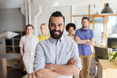 Happy young man over creative team in office Royalty Free Stock Photography