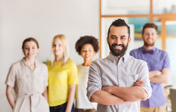 Happy young man over creative team in office Royalty Free Stock Image