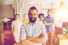 Happy young man over creative team in office. Business, startup, people and teamwork concept - happy young men with beard over creative team in office Royalty Free Stock Photo