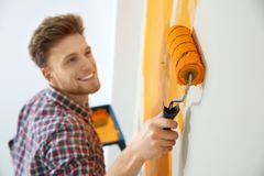 Happy young man painting wall indoors. Home repair royalty free stock images