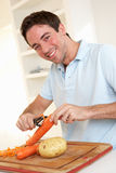 Happy young man peeling vegetable in kitchen Royalty Free Stock Images