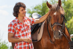 Happy young man petting his beautiful bay horse Stock Photo