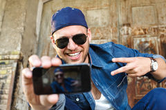 Happy young man photographing seflie with smart phone Stock Photos
