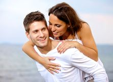 Happy Young Man Piggybacking His Girlfriend Stock Photos